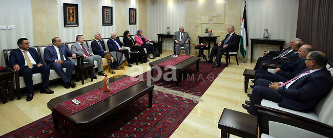 Palestinian Prime Minister, Rami Hamdallah, receives the annual report of the Anti-Corruption Commission for 2016, in the West Bank city of Ramallah, on April 13, 2017. Photo by Prime Minister Office