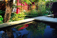 Reflective pond with sandstone edging and stepping stones surrounded by summer perennial planting with tree fern and various ferns as ground cover