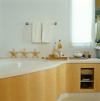This curved bath surround is made of plywood and pale stone