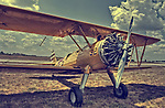 Close up of Stearman yellow vintage bi-plane on ground outdoors under summer sky with clouds