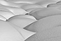 Patterns of shadow and shape created by deep snow over the Little Susitna River in Hatcher Pass in Southcentral Alaska. Afternoon. Winter.