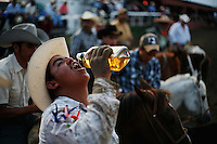 A charro takes a shot of tequila during a coleadero in Comfort, Texas. Drinking is frowned upon during an official charreada, but unofficial events are anything goes.