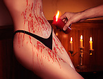 Sexy woman body covered in red drips falling from a candle in man's hand, sexual foreplay erotic photo