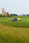 A blue tractor is working the fields, spreading fertilizer on the rich soil here in north central Illinois.