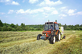 Farm tractor pulling round baler in field making round bales of hay, to be used to feed cattle