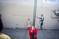 "Parents bring their children to the Woodside neighborhood of Queens in New York on Monday, October 14, 2013 to see the fourteenth installment of Banksy's graffiti art, ""What we do in life echoes in Eternity"". The elusive street artist is creating works around the city each day during the month of October accompanied by a satirical recorded message which you can hear by calling the number 1-800-656-4271 followed by  # and the number of artwork.  (© Richard B. Levine)"