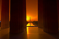 View through the columns of the Lincoln Memorial to the Reflecting Pool and Washington Monument at sunrise, Washington, District of Columbia, USA