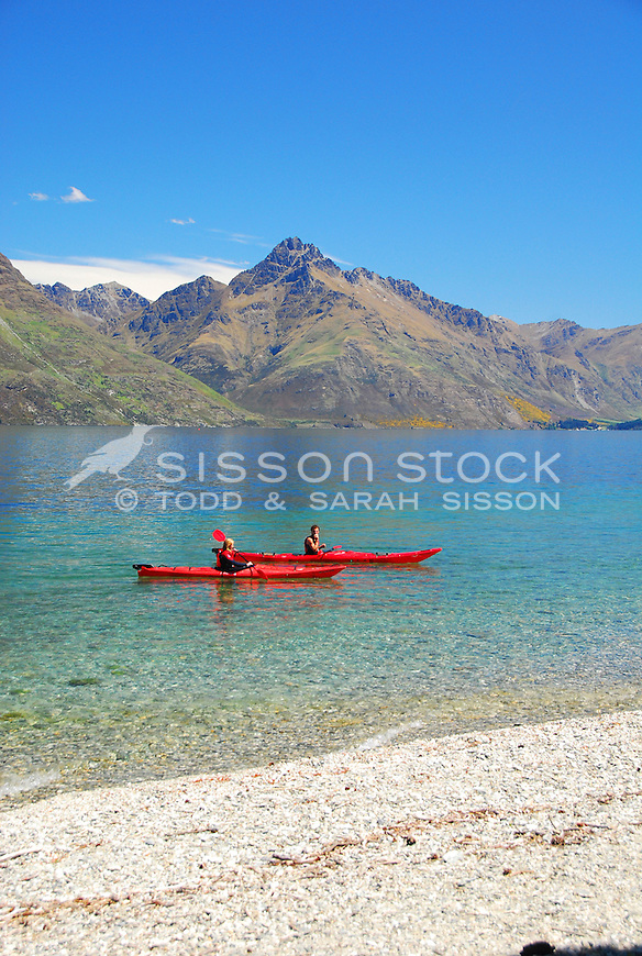 Two kayaks on Lake Wakatipu in summer with Walter Peak behind. Queenstown, New Zealand