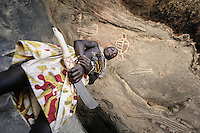 A foto of a teenage boy from the Mucubal tribe posing for a photograph and pretending to be the guardian of the old rock paintings on the wall of this cave in the Namibe Desert in Angola. Namibe, Angola