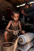 A young labourer making metal components at a factory.