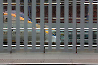 Eurostar train getting into St Pancras International, seen from an opposite platform, behind a wall of glass with grey opaque strips, with the Victorian architecture of the railways' terminus in the background, London, UK. Picture by Manuel Cohen