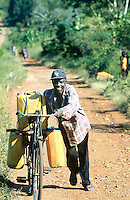 Uganda. Kayunga district. Gayaza. A man pushes his bike up the hill on a dirt road. He carries on his bicycle  heavy yellow jerrycans full of water. © 2004 Didier Ruef