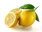 Fresh whole and cut lemons with leaves