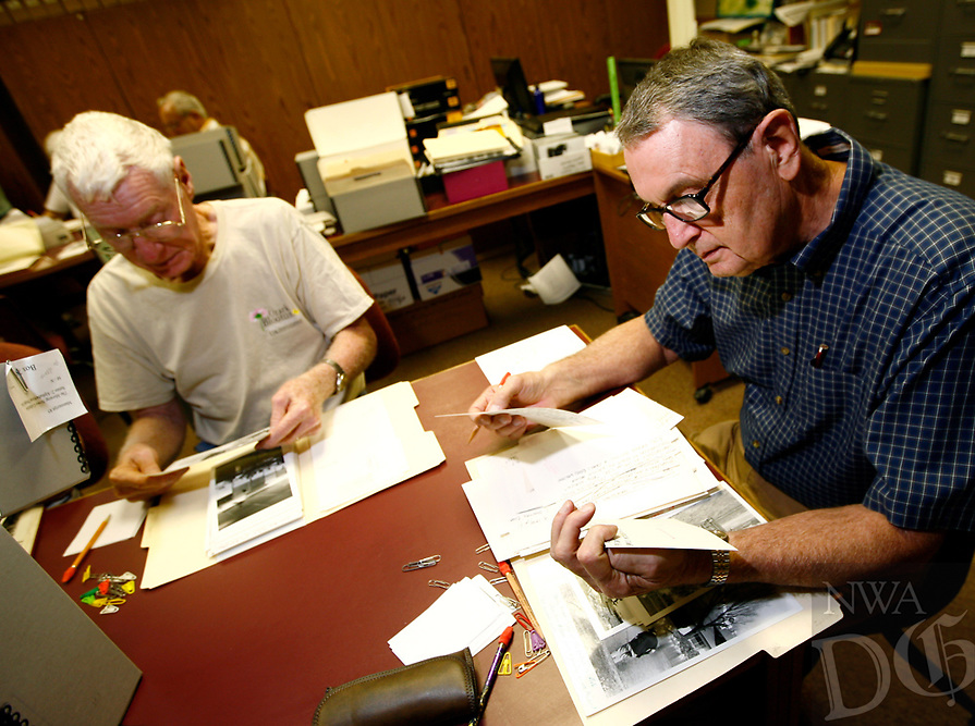 Arkansas Democrat-Gazette/JASON IVESTER --07/14/12--<br /> Truman Stamps (left) and Jim Morriss (cq), both of Springdale, flip through and study old photographs inside the Shiloh Musuem of Ozark History in Springdale on Saturday, July 14, 2012. The pair are part of a group that examines and identifies missing information in the archives of photos consisting of more than 500,000 images.