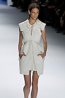 Aymeline Valade walks runway in a white super pique sleeveless peplum coat with oversized hood and cutout pockets over white textured silk slip dress, by Vera Wang, for the Vera Wang Spring 2012 collection, during Mercedes-Benz Fashion Week Spring 2012.