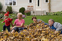 Happy Senior Grandparents with Kid Girl and Mother in Autumn Leaves