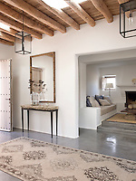 Th synergy of traditional and contemporary materials works beautifully in the house. Here the beamed wooden ceiling contrasts with the polished grey concrete floor and whitewashed walls