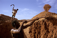 Workers dig into a mud pit to make adobe bricks in the village of Bani in the Sahel region of northern Burkina Faso.