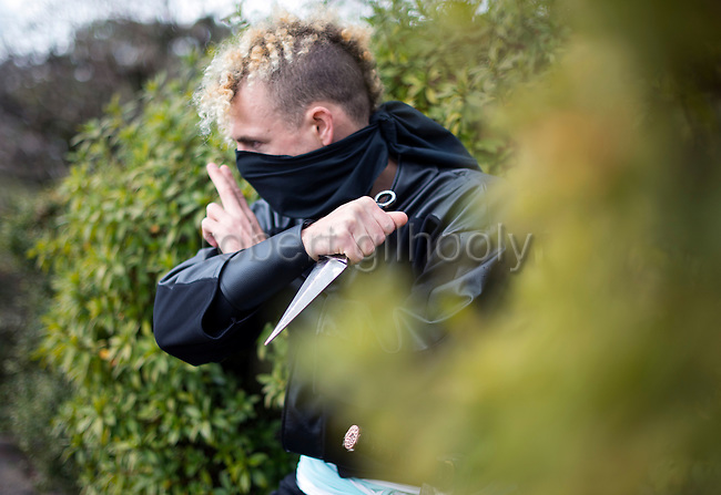 """Ninja Chris  """"Sora"""" O'Neil gets ready to pounce in the grounds of Nagoya Castle, Aichi Prefecture Japan on Feb. 23, 2017. O'Neil is one of the eight ninja corps who roam the avenues of the castle and Nagoya Airport, jumping from behind trees and bushes to surprise visitors. ROB GILHOOLY PHOTO"""