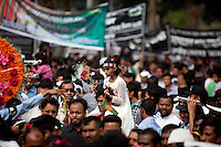 A Bangladeshi child sits on the shoulder of her father as they along with others stand in a queue to pay homage at the Dhaka Central Shaheed Minar, or Martyr's Monuments on International Mother Language Day in Dhaka, Bangladesh, Saterday, Feb. 21, 2015.