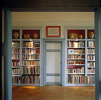 Recessed bookshelves, which display a collection of books and pottery, surround a doorway leading from the landing into a secret storage room