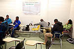 Alie Kamara, center, stretches as fellow classmates at Montgomery College, including Elhadj Diebate, far left, Samuel Hadgu, left, Elio Perdomo, right, and Tony Jones, far right, begin work on their group final project in their Basic Writing II class at the Takoma Campus on Dec. 11, 2012. If students pass this class, it allows them to progress to the college level english program. Otherwise students will face the decision to take the remedial class again or drop out.