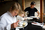 Foreign Cinema chef and owner, John Clark, reviews the wine menu as his kids, Magnus, 10, and Pearl, 3, eat dinner at the restaurant, in San Francisco, Ca., on Friday, June 12, 2009..
