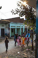 Commercial Sex Workers' children and Guria's staff teachers walk past brothels in the Shivdaspur red light area in Varanasi, Uttar Pradesh, India on 20 November 2013. The children growing up in brothels come to Guria's Non-Formal Education centers to spend their days playing, learning and doing art projects, often refusing to return to their homes at the end of the day.