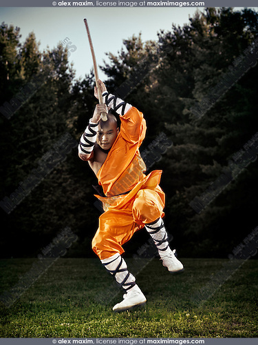 Portrait of a Shaolin warrior monk in mid-air jump with a staff