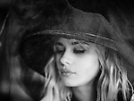Vignetted shot of blonde female model wearing a hat shot through a veil eyes closed