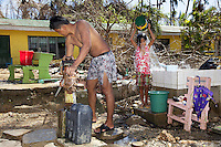 Philippines. Province Eastern Samar. Hernani. Central Elementary School. The building was destroyed and heavily flooded by typhoon Haiyan's winds and storm surge. Corporal Vilbert C. Paculanang of the Philippine Army takes washes himself in the school's courtyard. The girl Guvac Ogaya rinse soap by pouring a bucket of water on her body. Typhoon Haiyan, known as Typhoon Yolanda in the Philippines, was an exceptionally powerful tropical cyclone that devastated the Philippines. Haiyan is also the strongest storm recorded at landfall in terms of wind speed. Typhoon Haiyan's casualties and destructions occured during a powerful storm surge, an offshore rise of water associated with a low pressure weather system. Storm surges are caused primarily by high winds pushing on the ocean's surface. The wind causes the water to pile up higher than the ordinary sea level. 25.11.13 © 2013 Didier Ruef