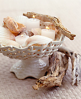 Detail of candles, sea shells and drift wood in a ceramic basket