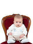 Humorous photo of a four month old baby boy sitting in a chair like a king on a throne