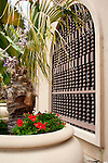Large potted palm stree with red flowers with slatted window