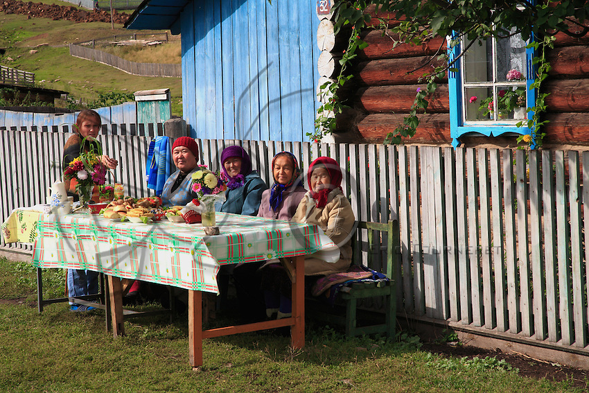 """In front of an isba, babushkas in multi-colored scarves compete for the prize of flowering village.  The national drink of Bashkir is a sort of mead made from plants called """"hitabalé""""."""