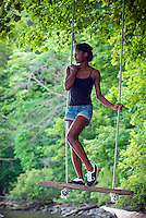 Young African American woman standing on rope swing