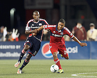 New England Revolution defender Jose Goncalves (23) disrupts Chicago Fire substitute forward Quincy Amarikwa (24) as he brings the ball forward.  In a Major League Soccer (MLS) match, the New England Revolution (blue) defeated Chicago Fire (red), 2-0, at Gillette Stadium on August 17, 2013.
