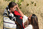 A Native American Sioux Indian women lovingly caressing the head of her daughter wrapped in a blanket