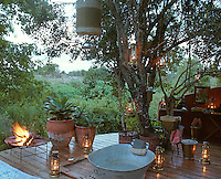 Washing at the safari camp takes place in a tin bath on a wooden decking beneath a shower suspended from a tree lit by storm lanterns
