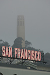 San Francisco's neon sign greets passengers getting off the ferries on the waterfront with Coit Tower in the background.