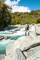 Young female, woman, tramper enjoying scenic and wild Perth River, South Westland, West Coast, South Westland, New Zealand, NZ