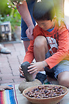 Nico Chow of Palo Alto grinds cracked acorns in a stone pestle during acorn preparation.