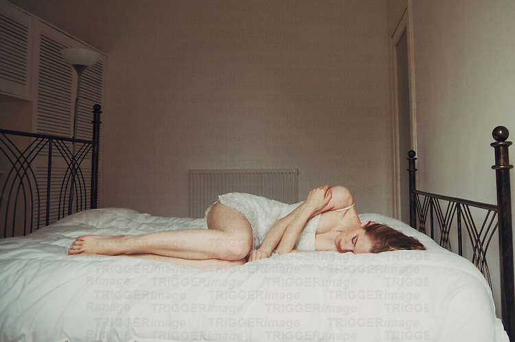 Young woman lying in bed in white room