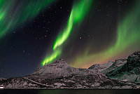 Strong multicolored Northern lights over jagged snow covered mountains. (Photo by Travel Photographer Matt Considine)