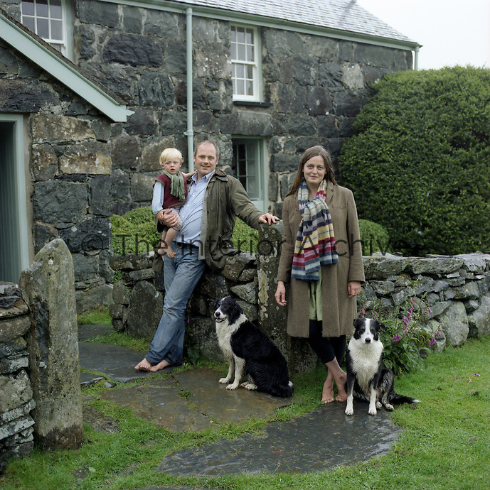 Portrait of architects Johnathan Holland and Jane Hackett  with their son and dogs