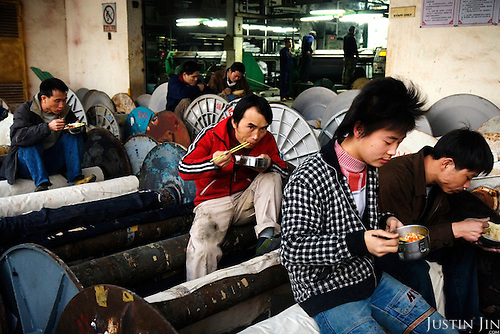 "Denim textile workers eat while sitting on giant spindles at a factory in Zhongshan city, China. .This picture is part of a photo and text story on blue jeans production in China by Justin Jin. .China, the ""factory of the world"", is now also the major producer for blue jeans. To meet production demand, thousands of workers sweat through the night scrubbing, spraying and tearing trousers to create their rugged look. .At dawn, workers bundle the garment off to another factory for packaging and shipping around the world..The workers are among the 200 million migrant labourers criss-crossing China.looking for a better life, at the same time building their country into a.mighty industrial power."