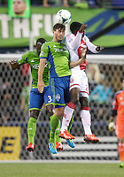 Brad Evans, center, of the Seattle Sounders FC battles Jose Valencia, right, of the Portland Timbers for the ball during play at CenturyLink Field in Seattle Saturday August, 3, 2013. The Sounder won the match 1-0.