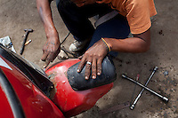 A man repairs a moto taxi on Tuesday, Apr. 14, 2009 in Ventanilla, Peru.
