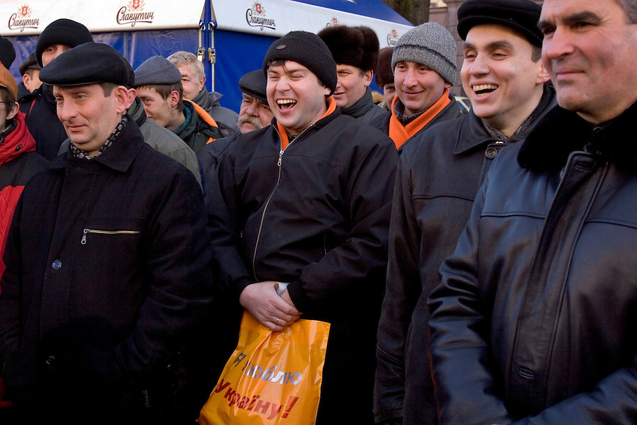 Kiev, Ukraine, 25/12/2004..The third and final round of Ukraine's disputed Presidential election. Supporters of candidate Viktor Yushchenko laughing at a satirical campaign video in the street.