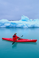 Kayaker paddles around a floating iceberg in Nellie Juan Lagoon in Prince William Sound, Alaska.